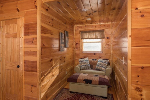 Reading nook with a large chair in the second bedroom at Moonshine Memories, a 2 bedroom cabin rental located in Gatlinburg