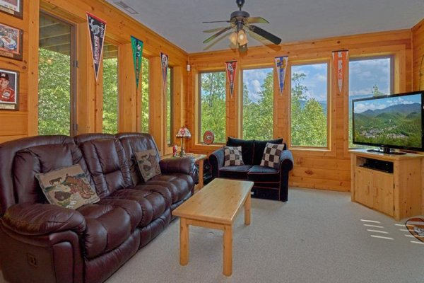 TV, sofa, and chair in the game room at Wagon Wheel Cabin, a 3 bedroom cabin rental located in Pigeon Forge