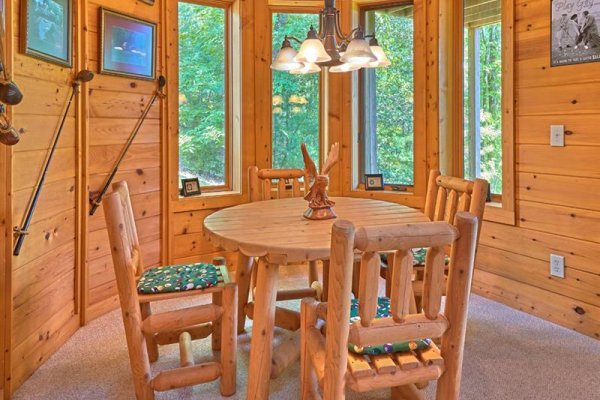Log table with four chairs in the game room at Wagon Wheel Cabin, a 3 bedroom cabin rental located in Pigeon Forge