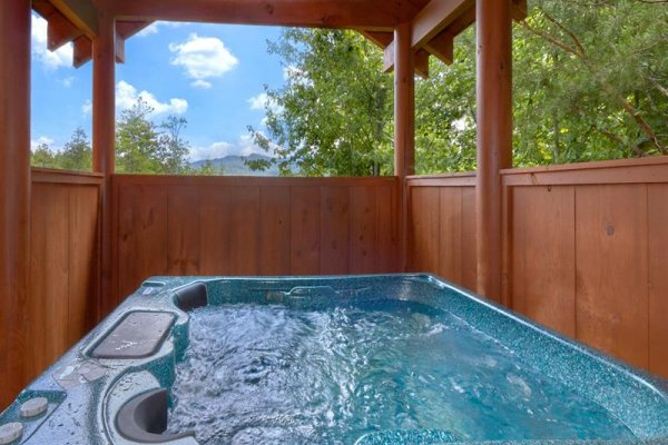 Hot tub on a covered deck with privacy fencing at Wagon Wheel Cabin, a 3 bedroom cabin rental located in Pigeon Forge