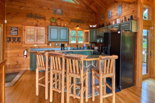 Kitchen with breakfast bar seating for four at Wagon Wheel Cabin, a 3 bedroom cabin rental located in Pigeon Forge