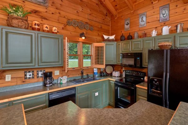 Kitchen with black appliances and an island at Wagon Wheel Cabin, a 3 bedroom cabin rental located in Pigeon Forge