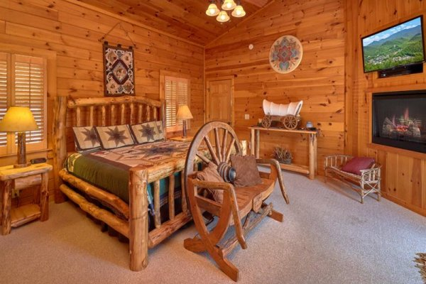 Bedroom on the main floor with a king bed, bench, fireplace, and TV at Wagon Wheel Cabin, a 3 bedroom cabin rental located in Pigeon Forge