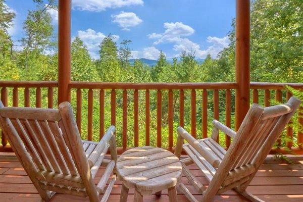 Rocking chairs on a covered deck at Wagon Wheel Cabin, a 3 bedroom cabin rental located in Pigeon Forge