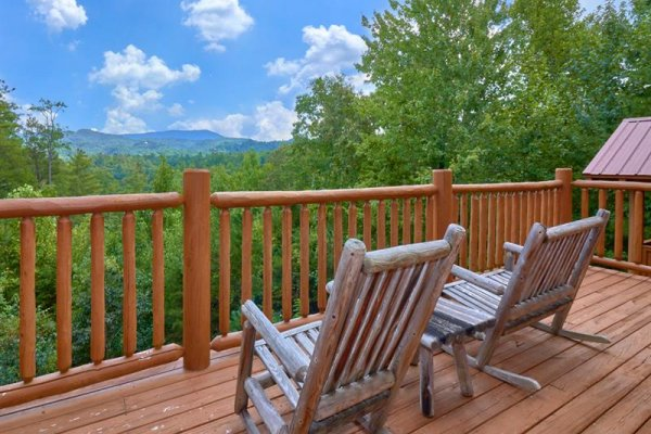Rocking chairs on a deck overlooking the mountains at Wagon Wheel Cabin, a 3 bedroom cabin rental located in Pigeon Forge