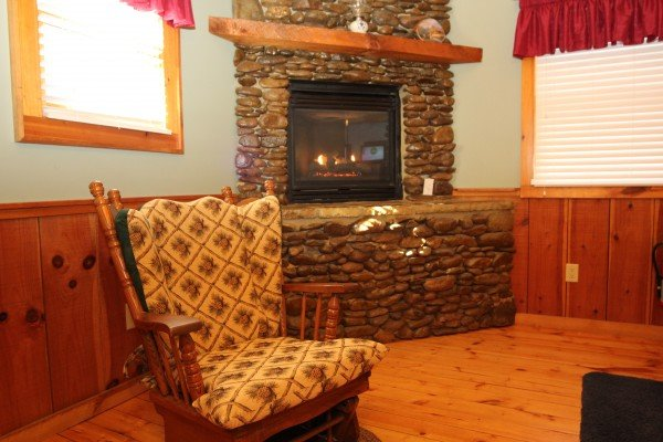 Fireplace and rocking chair in the second bedroom at Bear's Lair, a 2-bedroom cabin rental located in Pigeon Forge