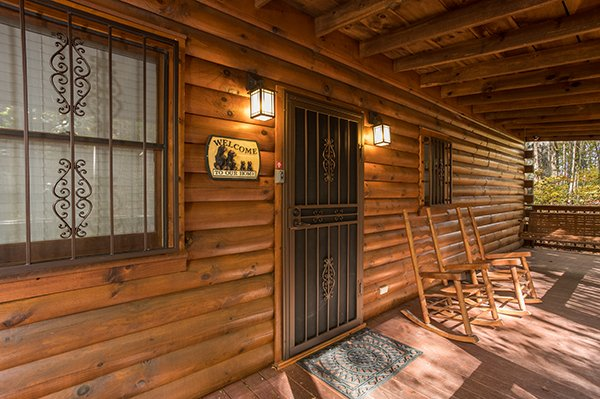 Front door with rocking chairs on a covered deck at Bear's Lair, a 2-bedroom cabin rental located in Pigeon Forge