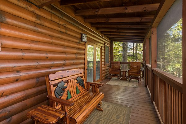 Gliding bench and rockers on the covered porch at Bear's Lair, a 2-bedroom cabin rental located in Pigeon Forge