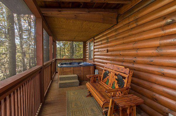 Hot tub and glider bench on a covered deck at Bear's Lair, a 2-bedroom cabin rental located in Pigeon Forge