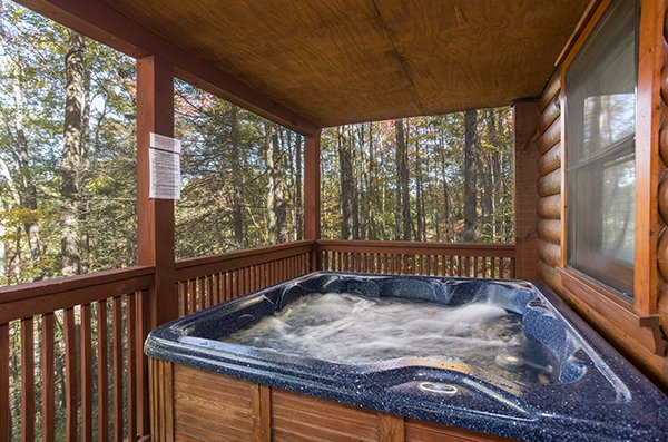 Hot tub on the covered desk at Bear's Lair, a 2-bedroom cabin rental located in Pigeon Forge