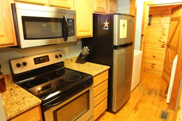 Stainless steel stove, above range microwave, and fridge at Bear's Lair, a 2-bedroom cabin rental located in Pigeon Forge