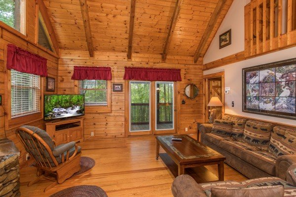 Living room with glider, sofa, and television at Bear's Lair, a 2-bedroom cabin rental located in Pigeon Forge