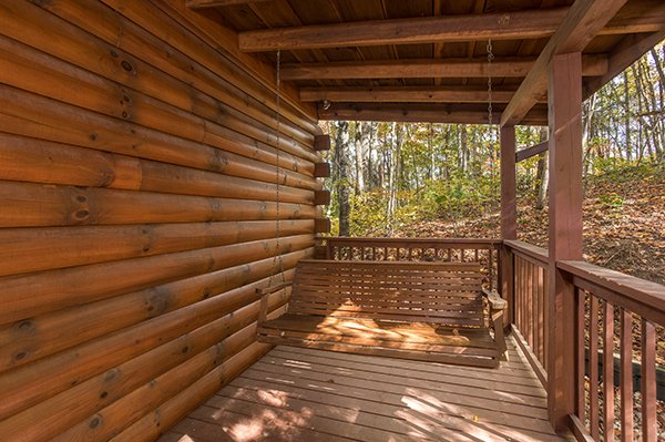 Porch swing on a covered deck at Bear's Lair, a 2-bedroom cabin rental located in Pigeon Forge