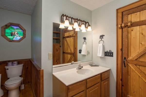 Second bathroom with a custom stained glass window at Bear's Lair, a 2-bedroom cabin rental located in Pigeon Forge