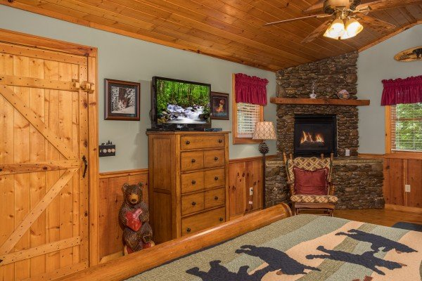 Bedroom with a stone fireplace, television, and dresser at Bear's Lair, a 2-bedroom cabin rental located in Pigeon Forge