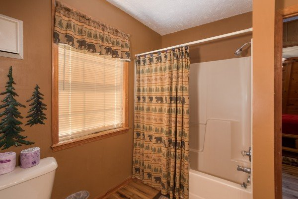 A bathroom with a tub and shower at Cozy Mountain View, a 1-bedroom cabin rental located in Pigeon Forge