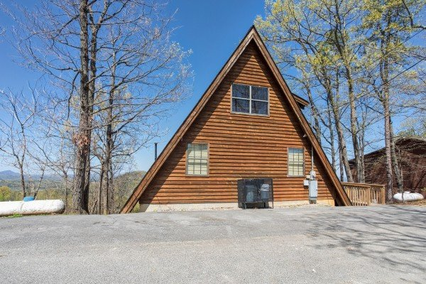 Flat paved parking and exterior of an A-frame cabin at Cozy Mountain View, a 1-bedroom cabin rental located in Pigeon Forge