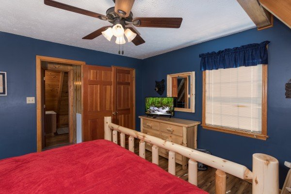 Bedroom with king-sized bed, dresser, and television at Cozy Mountain View, a 1-bedroom cabin rental located in Pigeon Forge