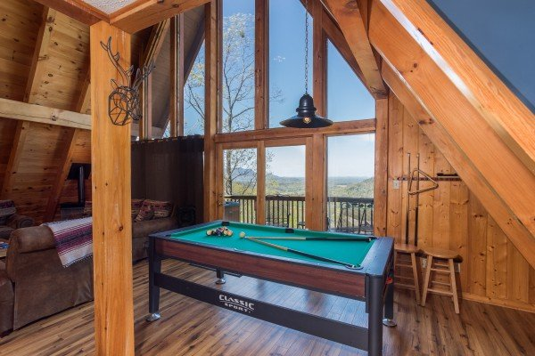 A pool table in the game loft at Cozy Mountain View, a 1-bedroom cabin rental located in Pigeon Forge