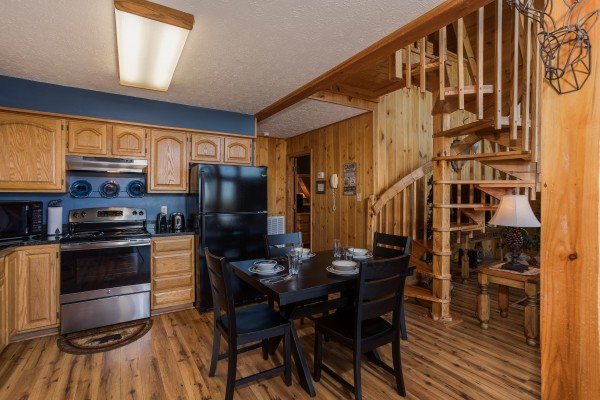 Kitchen with stainless and black appliances and dining room seating for four at Cozy Mountain View, a 1-bedroom cabin rental located in Pigeon Forge