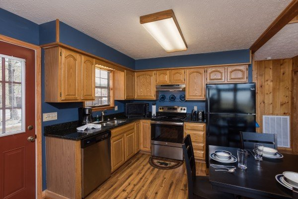 Kitchen with black and stainless appliances and dining space for four at Cozy Mountain View, a 1-bedroom cabin rental located in Pigeon Forge