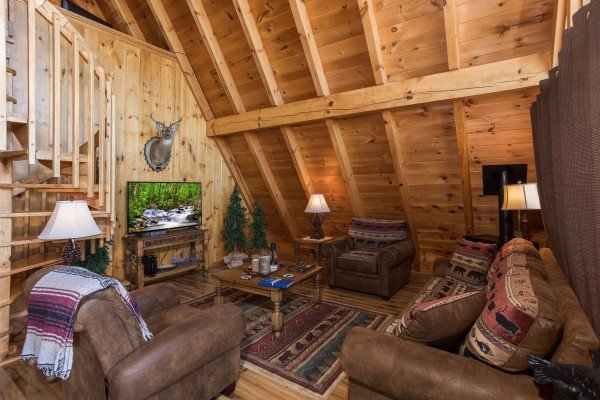 Living room with large TV, two chairs, and a sofa at Cozy Mountain View, a 1-bedroom cabin rental located in Pigeon Forge