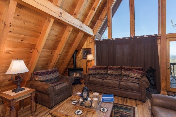 Living room with a couch, chair, and large picture windows at Cozy Mountain View, a 1-bedroom cabin rental located in Pigeon Forge