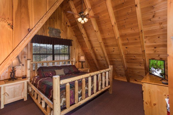 King-sized log bed in the loft at Cozy Mountain View, a 1-bedroom cabin rental located in Pigeon Forge