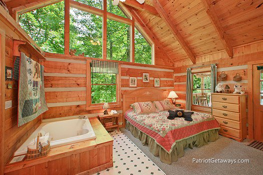 King-sized bed with two night stands and jacuzzi tub in bedroom at Call of the Wild, a 1-bedroom cabin rental located in Pigeon Forge