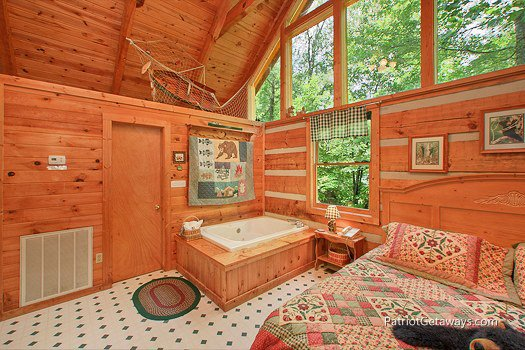 Jacuzzi tub next to bed at Call of the Wild, a 1-bedroom cabin rental located in Pigeon Forge
