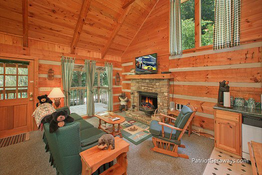 Living room with stone fireplace and television at Call of the Wild, a 1-bedroom cabin rental located in Pigeon Forge