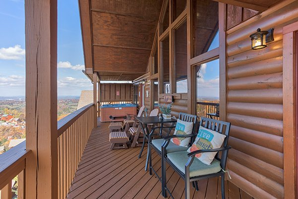 Benches and lounge chairs on the covered deck at The Bear's House, a 4 bedroom cabin rental in Pigeon Forge