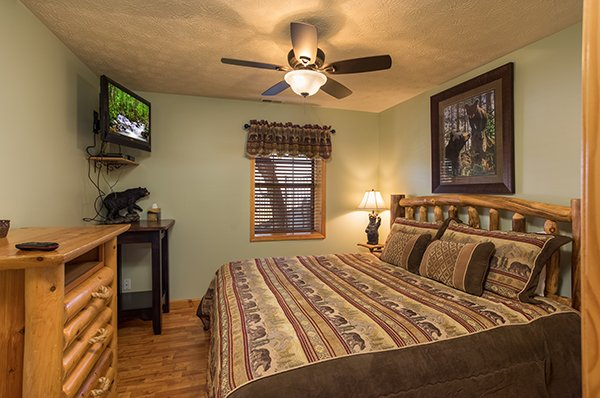 First king bedroom with dresser and TV at The Bear's House, a 4 bedroom cabin rental in Pigeon Forge