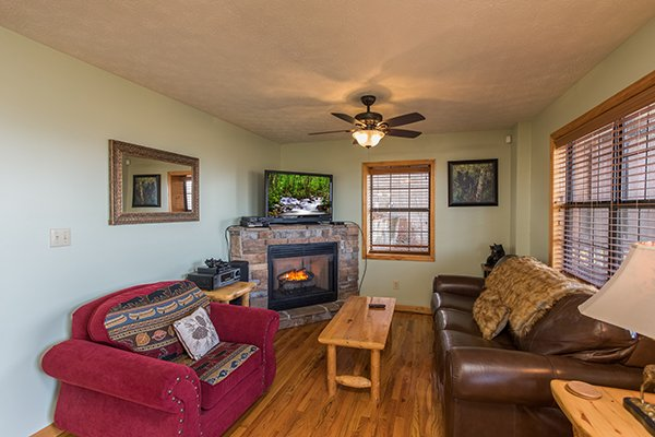 Den with a sofa bed, fireplace, and TV in the game room at The Bear's House, a 4 bedroom cabin rental in Pigeon Forge