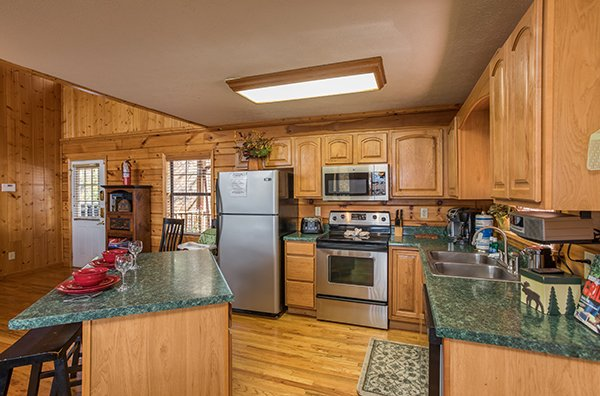 Kitchen with stainless appliances and island seating at The Bear's House, a 4 bedroom cabin rental in Pigeon Forge