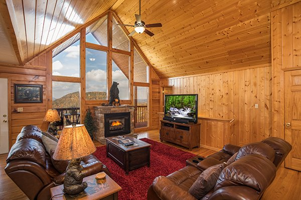 Living room with high windows, fireplace, and TV at The Bear's House, a 4 bedroom cabin rental in Pigeon Forge