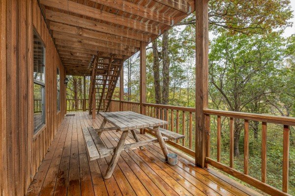Picnic table on the deck at Pampered Campers, a 3 bedroom cabin rental located in Pigeon Forge