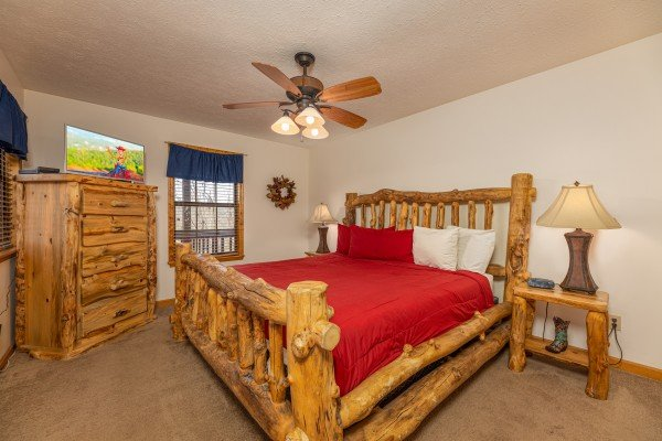 King log bed with dresser, tv, and night stands at Pampered Campers, a 3 bedroom cabin rental located in Pigeon Forge