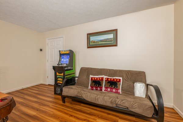 Futon and video game at Pampered Campers, a 3 bedroom cabin rental located in Pigeon Forge