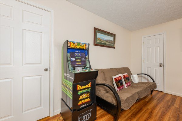 Game and futon at Pampered Campers, a 3 bedroom cabin rental located in Pigeon Forge