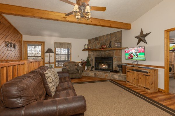 Living room with fireplace and TV at Pampered Campers, a 3 bedroom cabin rental located in Pigeon Forge