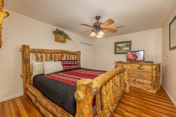Bedroom with log bed, dresser, TV at Pampered Campers, a 3 bedroom cabin rental located in Pigeon Forge