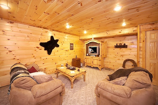 first floor seating area with sleeper sofa at smoky bears creek a 2 bedroom cabin rental located in pigeon forge