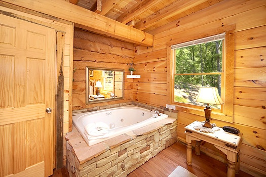 king bedroom with jacuzzi tub at smoky bears creek a 2 bedroom cabin rental located in pigeon forge