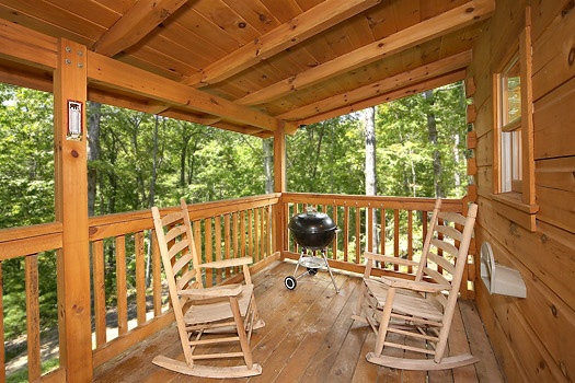 main level deck with grill and rockers at smoky bears creek a 2 bedroom cabin rental located in pigeon forge
