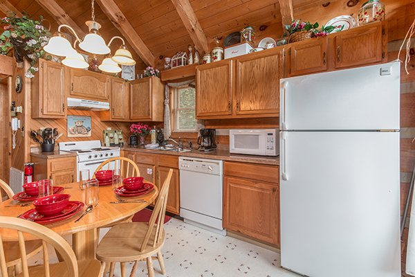 Kitchen with white appliances and dining room for four Bare Hugs, a 1-bedroom cabin rental located in Pigeon Forge
