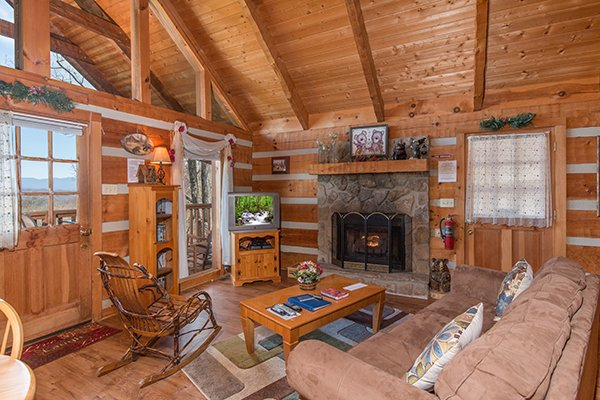 Living room with gas fireplace and television at Bare Hugs, a 1-bedroom cabin rental located in Pigeon Forge