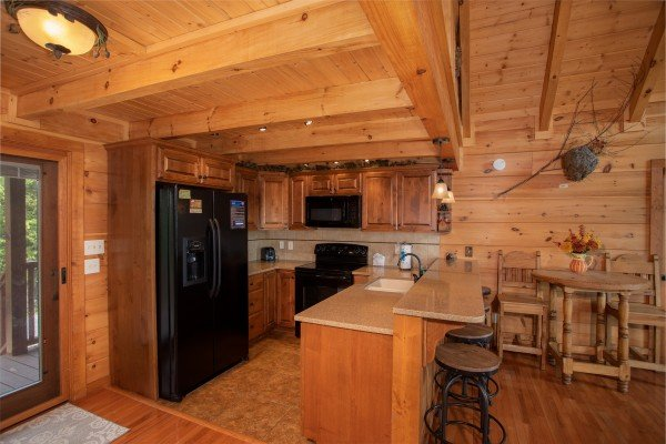 Kitchen with black appliances, counter top seating, and a high top dining table at Cedar Creeks, a 2-bedroom cabin rental located near Douglas Lake