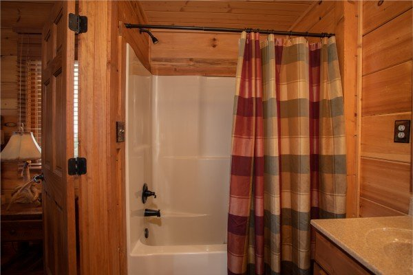 Bathroom with a tub and shower at Cedar Creeks, a 2-bedroom cabin rental located near Douglas Lake
