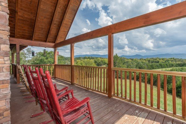 Rocking chairs lined up on a covered deck with lake and mountain views at Cedar Creeks, a 2-bedroom cabin rental located near Douglas Lake